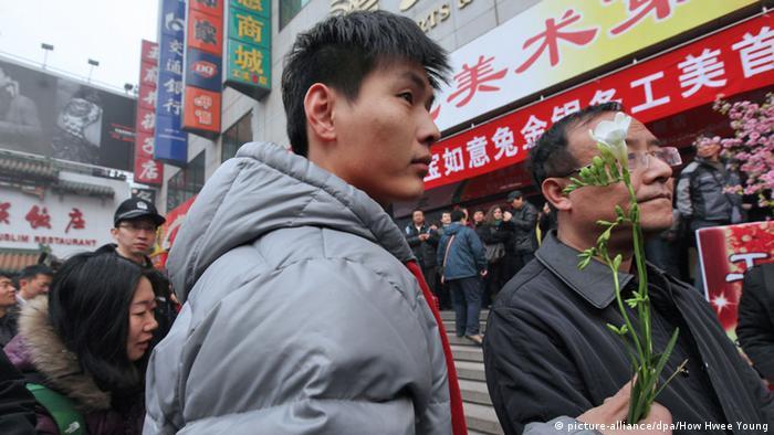 Jasminrevolution in China. Ein Mann hält eine Blume in der Hand