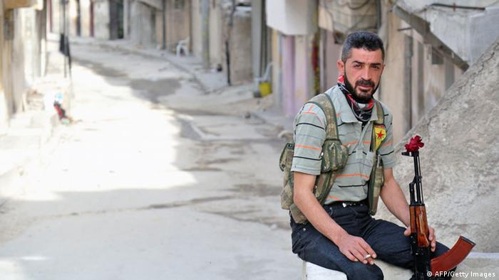 Rebel fighter of the Syrian Kurdish Popular Protection Units (YPG) poses with a flower in his Russian made 'AK-47'