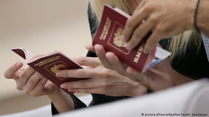 Руки людей с российскими паспортами