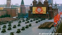 Militärfahrzeuge und marschierende Soldaten während einer Parade auf dem Roten Platz in Moskau am 09. Mai 1985 zum Tag des Sieges über Hitler-Deutschland 1945. Im Hintergrund ein Großplakat an der Fassade des Historischen Museums mit dem Symbol des Warschauer Paktes. Links Kremltürme. +++picture-alliance/Tass