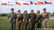 Soldaten posieren in verschiedenen Uniformen vor den Flaggen der sieben Mitgliedsländer des Warschauer Pakts (undatierte Aufnahme). Dem Warschauer Pakt hatten sich Bulgarien, DDR, Polen, Rumänien, Tschechoslowakei, Sowjetunion und Ungarn angeschlossen. +++picture-alliance/dpa