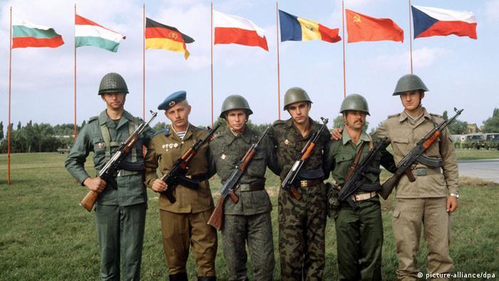 Soldados diante das bandeiras dos sete países signatários do Pacto de Varsóvia