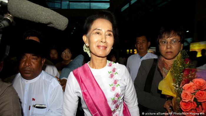 Myanmar's opposition leader Aung San Suu Kyi, center, walks upon her arrival at Yangon International Airport to depart for China, Wednesday, June 10, 2015, in Yangon, Myanmar (AP Photo/Khin Maung Win)