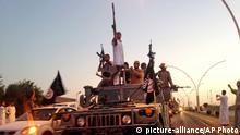 ARCHIV 2014 **** FILE - In this Monday, June 23, 2014 photo, fighters from the Islamic State group parade in a commandeered Iraqi security forces armored vehicle down a main road at the northern city of Mosul, Iraq. (AP Photo, File)