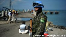 A Brazilian soldier of the MINUSTAH (United Nations Stabilization Mission in Haiti) peacekeeping contingent patrols in the Cite Soleil slum of Port-au-Prince on March 11, 2014. The Brazilian contingent counts 1,433 members, divided into engineering, headquarters, infantry troops and riot control, according to MINUSTAH. AFP PHOTO/Hector RETAMAL (Photo credit should read HECTOR RETAMAL/AFP/Getty Images)