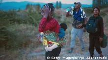 10.06.2015**** Bildunterschrift:A group of migrants walk on a road near the town of Demir Kapija on the way to the Serbian border on June 10, 2015. Macedonia has become one of the main transit routes for thousands of migrants from the Middle East and Africa, entering from neighboring Greece on their way to western European countries. AFP PHOTO / ROBERT ATANASOVSKI (Photo credit should read ROBERT ATANASOVSKI/AFP/Getty Images)