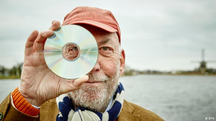 Immink holding a silver disc partly in front of his face
