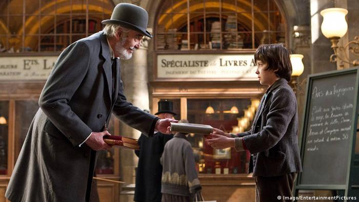 Filmszene aus Hugo Cabret mit Christopher Lee und Asa Butterfield. Lee reicht Butterfield ein Buch (Imago/EntertainmentPictures)
