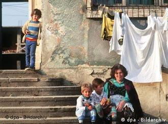 A mother sits outsides on the steps to her home with her children while laundry dries in the background