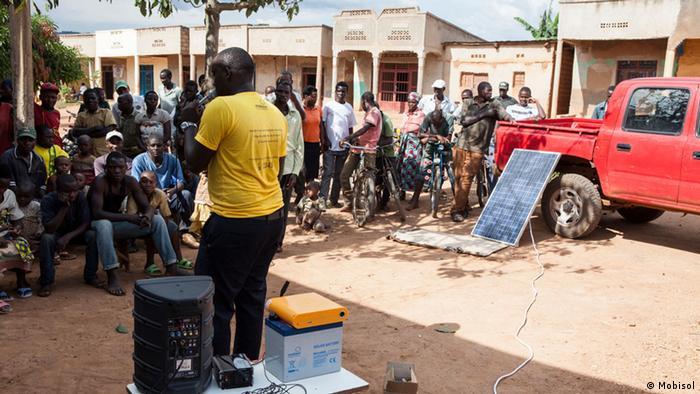 Auf einem Markt wird ein Solarsystem vorgestellt. (Foto Mobisol)