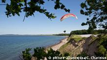 Ein Gleitschirmflieger fliegt am 29.05.2014 bei strahlendem Sonnenschein im Hangaufwind an der Steilküste der Ostsee am Weissenhäuser Strand (Schleswig-Holstein). Foto: Christian Charisius