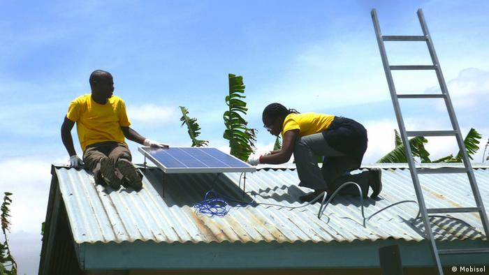 Peope in Ruanda set up solar panels on a roof. (Photo: Mobisol)