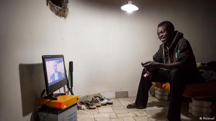 Ein Mann schaut auf seinem Solarset Fernsehen (Foto: Mobisol)