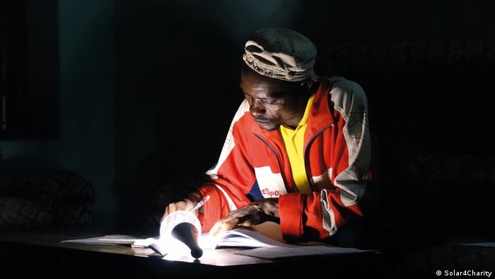 A man reads a book that is illuminated by a small light