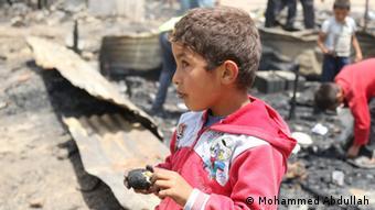 A young boy in eats a burnt potato