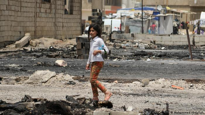 A young girl poses in the burned rubble of Jaharriyeh Camp