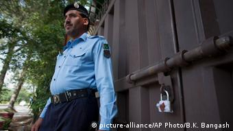 A Pakistani police officer stands guard outside a sealed 'Save the Children' office in Islamabad, Pakistan, Friday, June 12, 2015 (AP Photo/B.K. Bangash)
