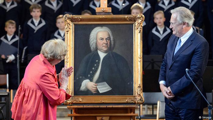 Painting of Bach, with choir boys in the background, Judith Scheide in pink applauding after the unveiling and the conductor John Eliot Gardiner looking on (Imago)