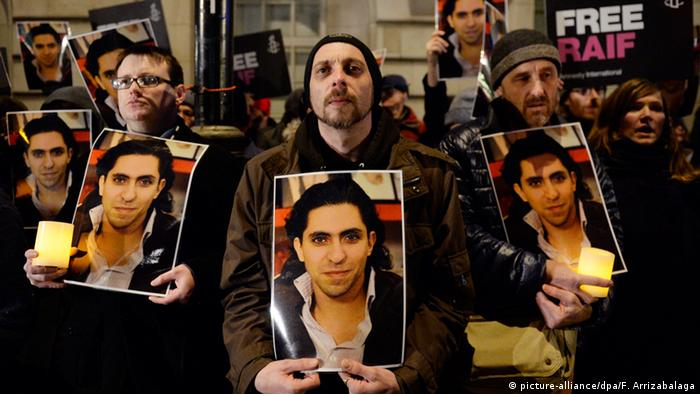 Protesters in London holding pictures of Badawi