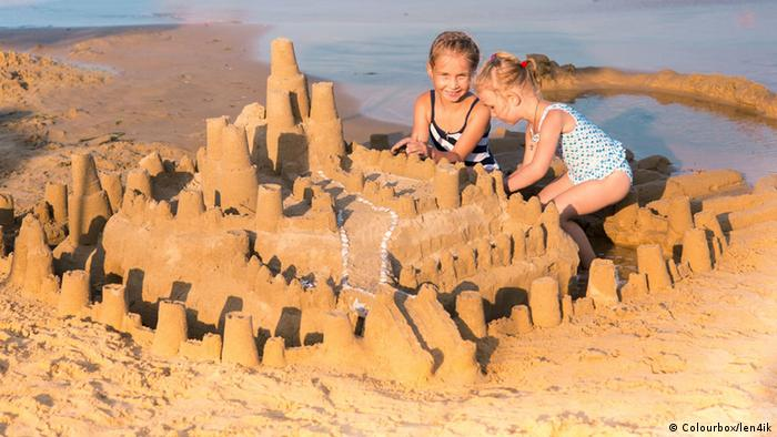 Девочки строят замок из песка
