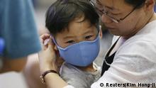 14.06.2015+++ A passenger puts a masks on her son to prevent contracting Middle East Respiratory Syndrome (MERS) at the Incheon International Airport in Incheon, South Korea, June 14, 2015. A South Korean hospital suspended most services on Sunday after being identified as the epicentre of the spread of a deadly respiratory disease that has killed 15 people since being diagnosed in the country nearly four weeks ago. REUTERS/Kim Hong-Ji