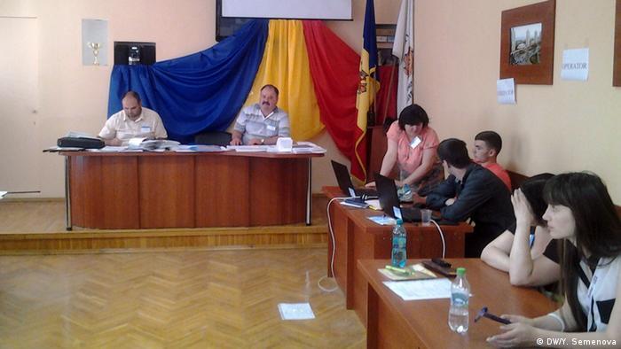 Работники сидят за столами на избирательном участке в Молдавии