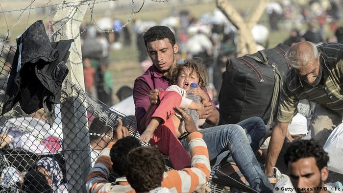 Syrians break a Turkish border fence as they flee conflict