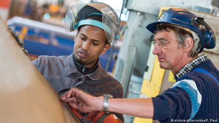 In einer Werkstatt erklärt ein Mann einem auszubildenden Flüchtling, wie er zu arbeiten hat.