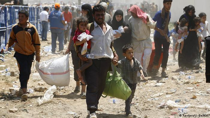 A Syrian refugee crosses the border into Tirkey, carrying his young daughter in his right arm, along with a bottle fo water; while in his left hand he holds a his son's Hand and a green bag of personal belongings.