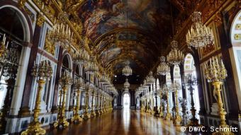 Longo corredor cheio de lustres , candelabros e decorações em ouro