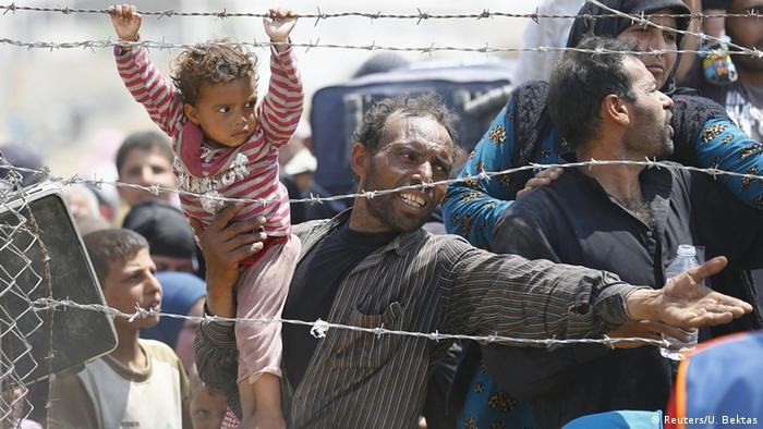 A Syrian refugee. at the Syrian-Turkish border, reaches through barbed-wire fencing while the toddler in his hand holds on to the barbed wire.