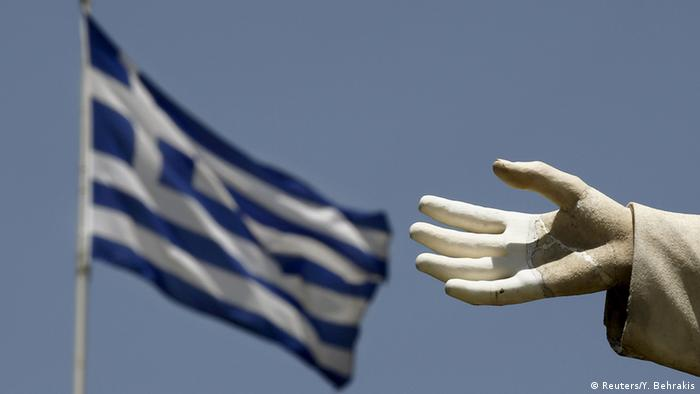 A Greek flag with a statue's hand in the foreground. (Photo: REUTERS/Yannis Behrakis)