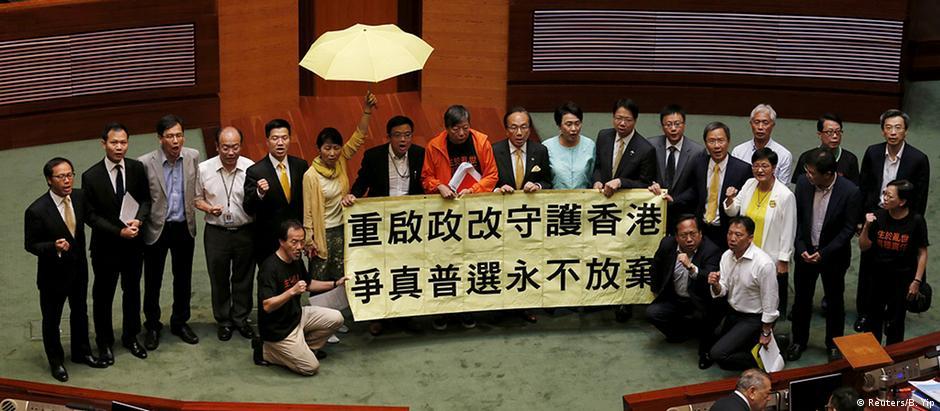 Deputados da oposição exibem faixa contra o projeto de lei no plenário do parlamento