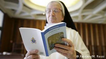 A nun reads a copy of Pope Francis' encyclical on the environment