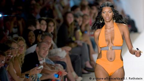 Woman in bright orange one-piece walking down a catwalk