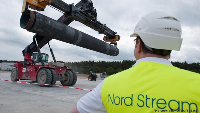 Рабочий в фирменной одежде Северного потока наблюдает за погрузкой трубы для газопровода