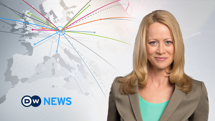 Female news presenter with blonde hair wearing a tan blazer, smiling next to the DW News logo