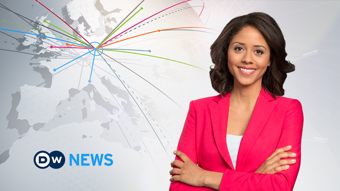 Female news anchor wearing a magenta blazer with folded arms smiling next to a DW News logo