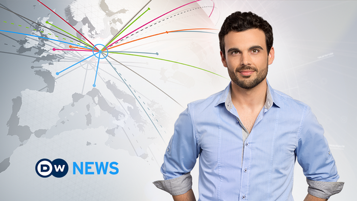 Male news presenter with causal shirt smiling next to DW News logo