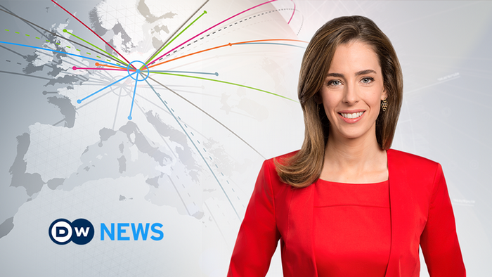 Female news anchor in a red blouse and blazer smiling next to a DW News logo