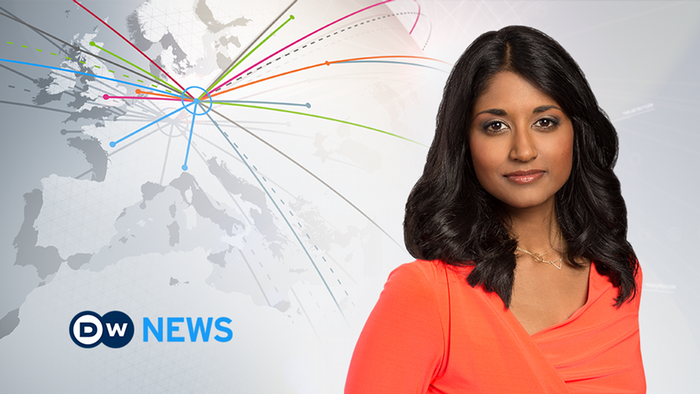 Female news anchor with long brown hair and orange blouse serious face next to DW News logo