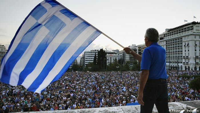 A protester waves a Greek flag at the entrance of the Greek parliament, during a rally calling on the government to clinch a deal with its international creditors