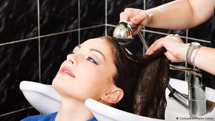 Seorang perempuan di salon, rambutnya sedang dicuci