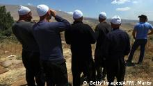 Bildunterschrift:A picture taken from the Israeli-annexed Golan Heights shows Druze men residing in Israel watching smoke rise in the horizon in the Syrian Druze village of Hader , on June 16, 2015. Al-Nusra Front, one of al-Qaeda's Syrian affiliate, are reportedly engaging offensive operations against Syrian government forces around Hader, located approximately 15 kms east of the Israeli-held Golan. AFP PHOTP / JALAA MAREY (Photo credit should read JALAA MAREY/AFP/Getty Images)