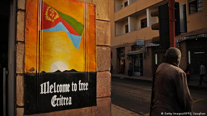 Poster in Asmara reading - welcome to Eritrea. Next to it, a man standing alone