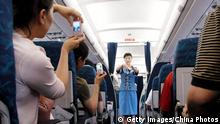 Bildunterschrift:CHENGDU, CHINA - JULY 26: (CHINA OUT) Passengers take pictures of a stewardess demonstrating how to fasten a seat belt on the first flight of the United Eagle Airlines on July 26, 2005 in Chengdu of Sichuan Province, southwest China. Private airline United Eagle Airlines has launched its maiden commercial flight on July 26, carrying passengers from Chengdu to Shenzhen in Guangdong Province. At least three private sector airlines have received approval from civil aviation authorities and plan to offer low-cost, no-frills services, including Eagle United in Chengdu, Spring International Airlines in Shanghai and Okay Airways, based in the Beijing area. (Photo by China Photos/Getty Images)