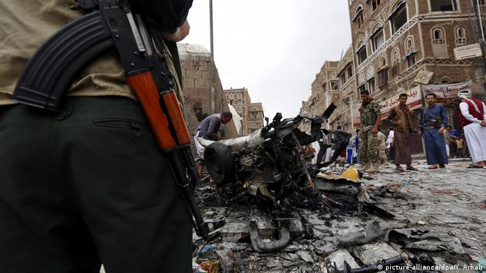 Yemenis gather around the wreckage at the scene of a car bombing which targeted a Shiite mosque in the old city of Sana'a, Yemen, 20 June 2015.