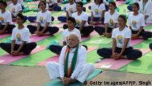 21.6.2015 Indian Prime Minister Narendra Modi (C) participates in a mass yoga session along with other Indian yoga practitioners to mark the International Yoga Day on Rajpath in New Delhi on June 21, 2015. Prime Minister Narendra Modi on June 21 hailed the first International Yoga Day as a new era of peace, moments before he took to a mat and joined thousands in the heart of New Delhi to celebrate the ancient Indian practice. AFP PHOTO / PRAKASH SINGH (Photo credit should read PRAKASH SINGH/AFP/Getty Images)