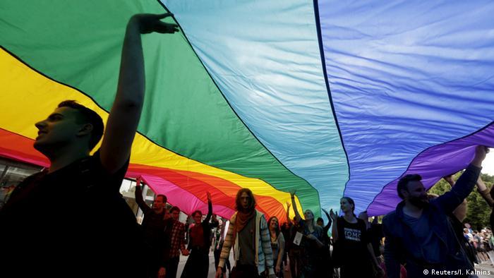 Unter einer riesigen Regenbogen-Fahne ziehen die Aktivisten der Schwulen und Lesben durch Riga (foto: reuters)