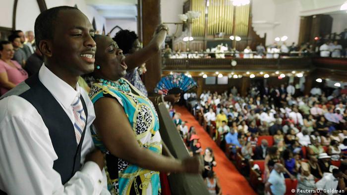 Pessoas cantam em tribuna de igreja durante culto religioso nos EUA